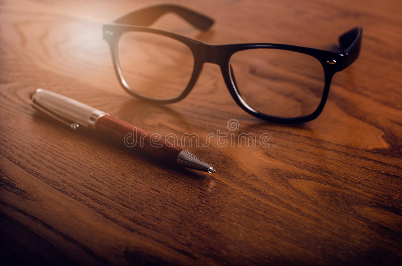 Glasses with pen and tablet on a wooden natural table. Home office. Concept of work in a office and accessories royalty free stock images