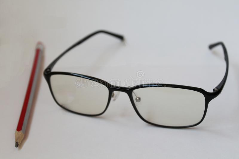 Glasses and pencil on white background stock image