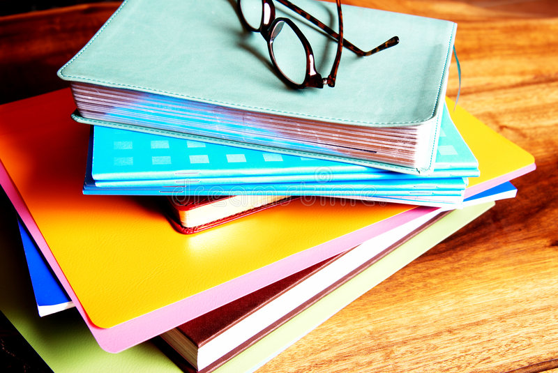 Glasses on a pile of books. Leopard patern reading glasses lying on a pile of books and files.Everything is lying on a wood table stock photo