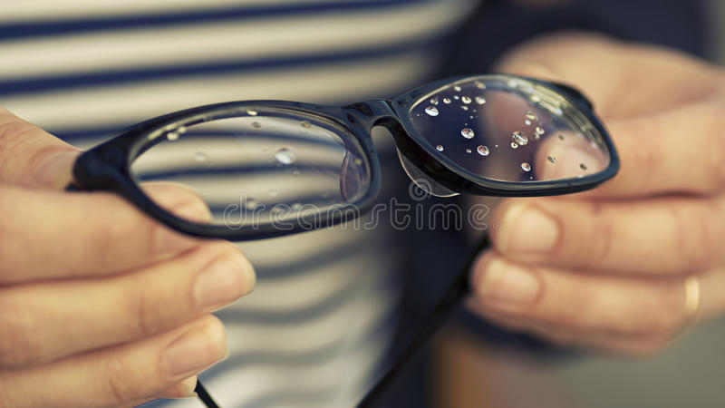 Glasses with rain drops. In the girl's hands royalty free stock images