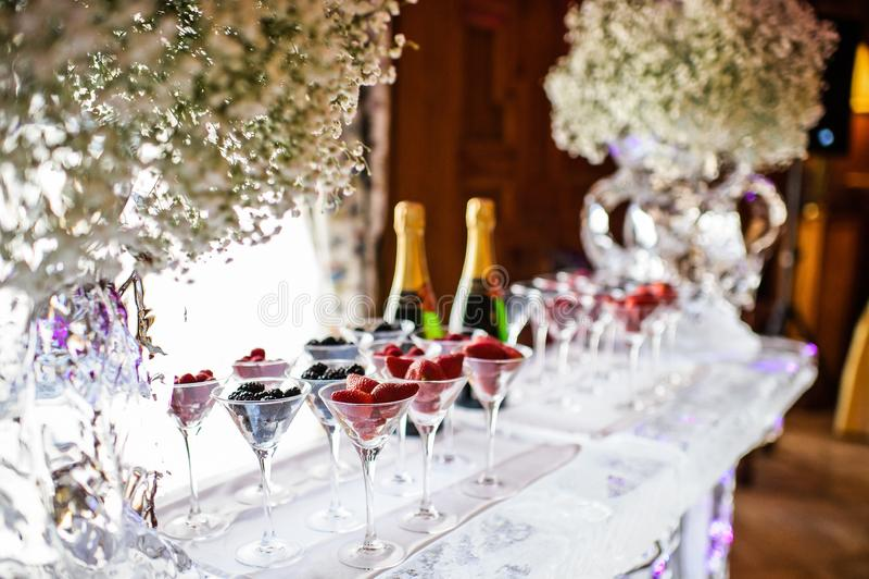 Glasses of raspberries, strawberries, blackberries on the ice bar. Gala dinner at the restaurant stock photography