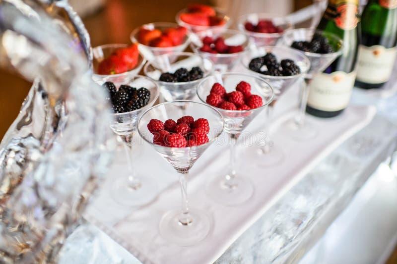 Glasses of raspberries, strawberries, blackberries on the ice bar. Gala dinner at the restaurant stock photo