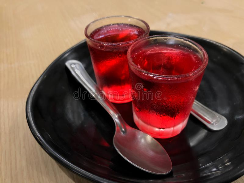 Glasses of red cold jelly pudding serving on black ceramic plate with silver spoon royalty free stock photography