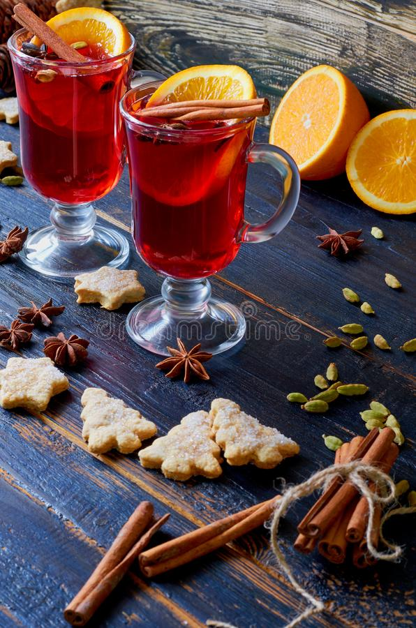 Glasses of red mulled wine decorated with Christmas cookies and various winter spices - anise stars, cinnamon on the black table royalty free stock photo
