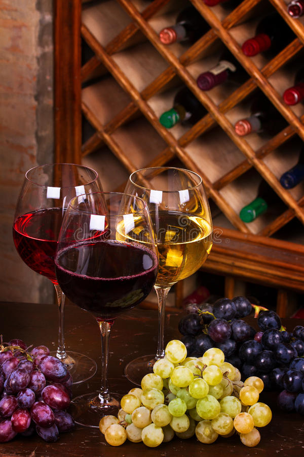 Glasses of red, rose and white wine with cheese, and grape in wine cellar stock images