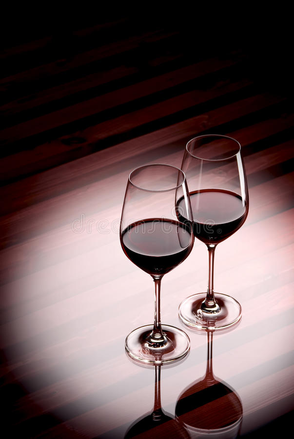 Glasses of red whine in an illumination royalty free stock photography