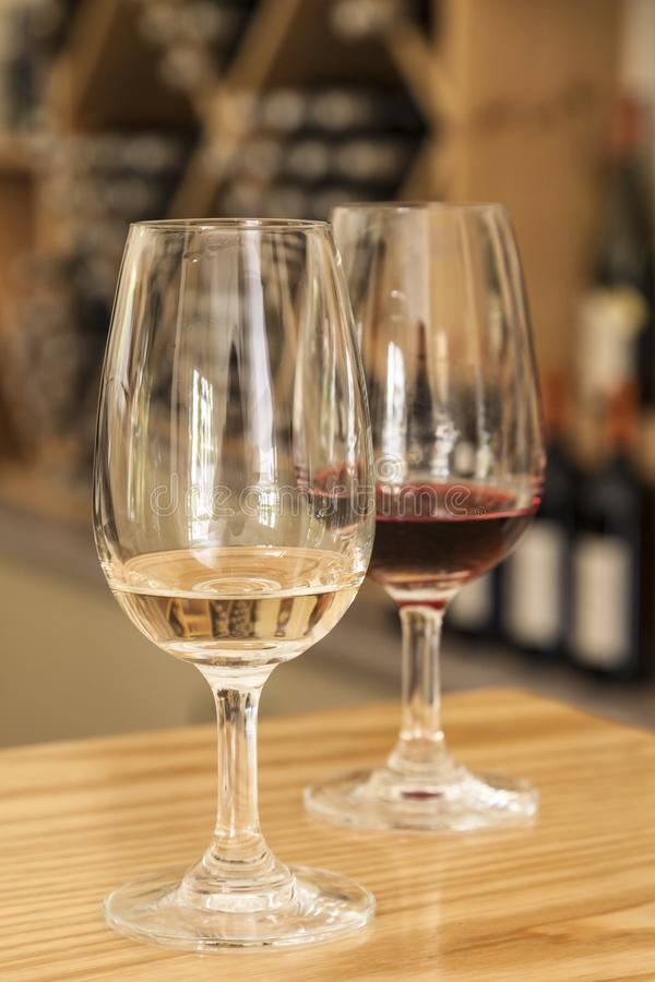 Glasses of red and white wine on table bar in winery tasting room with wine bottles in background royalty free stock images