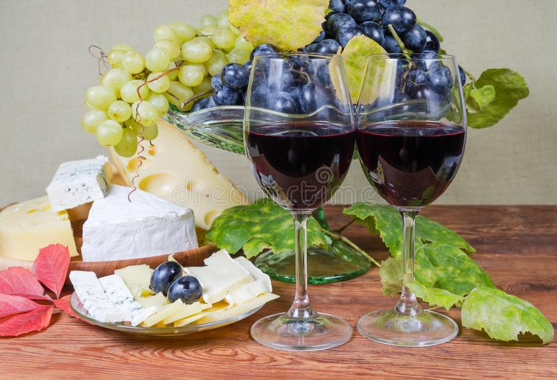Glasses of red wine against blue grapes and various cheese royalty free stock image