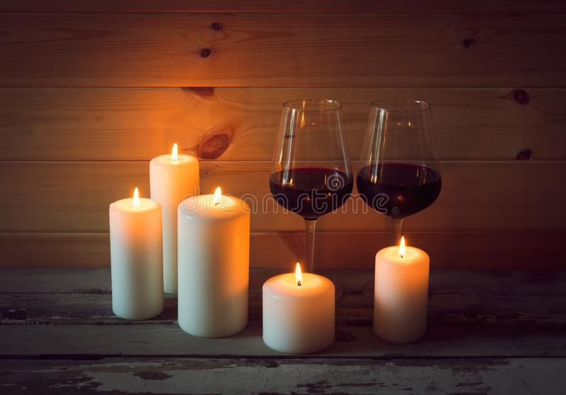 Glasses of red wine with candles on wooden background stock photography