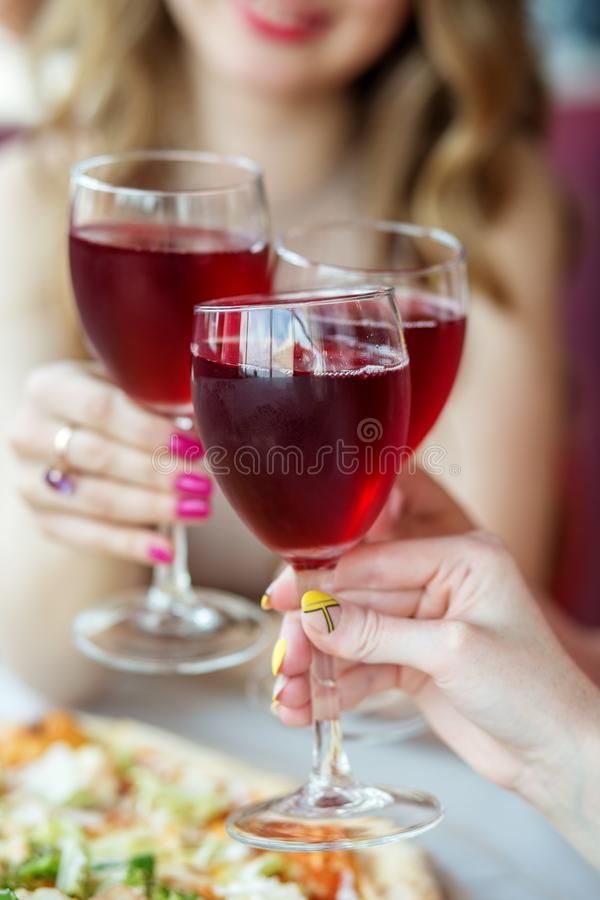 Glasses of red wine in female hands. Toast at a party. Vertical. Concept of alcohol, holiday stock photo