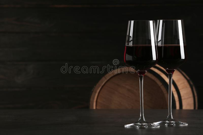 Glasses of red wine and wooden barrel on background. Space for text royalty free stock image