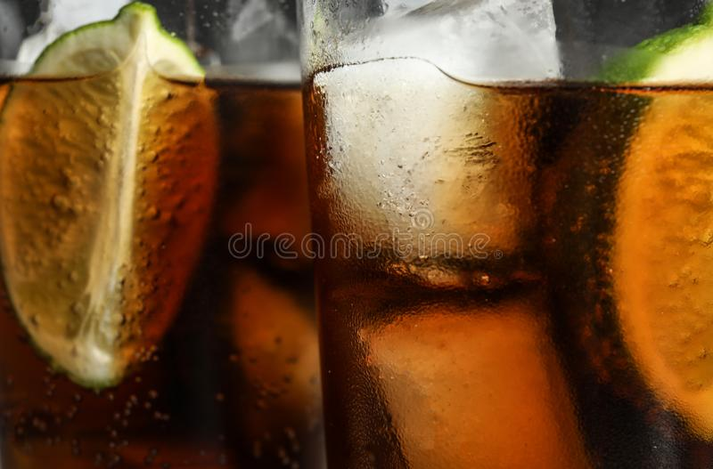Glasses of refreshing soda drinks with ice cubes and lime. Closeup stock photo