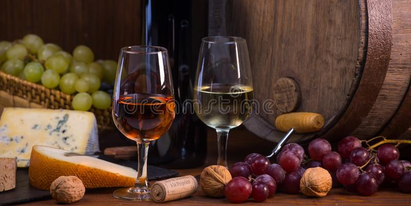 Glasses of rose and white wine cheeses grapesand barrel brown background. Glasses of rose and white wine cheeses grapesand barrel on brown wooden background royalty free stock photo