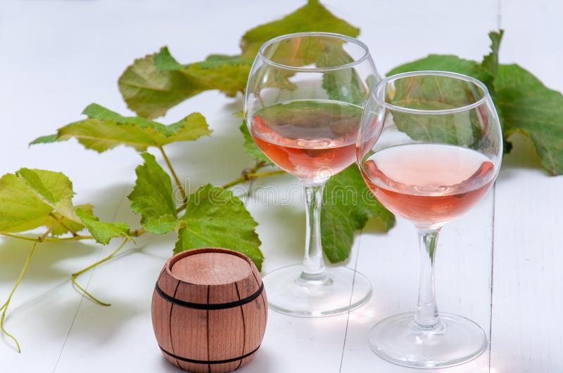 Glasses with rose wine and a wooden barrel with a branch and leaves of grapes on a white wooden table. royalty free stock photo