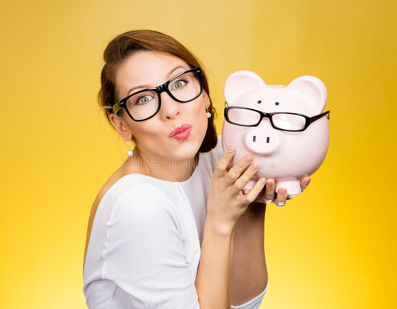 Glasses sale concept. Happy woman kissing piggy bank wearing eyewear glasses royalty free stock images