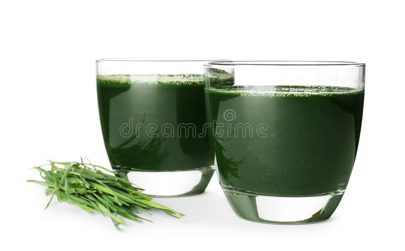 Glasses of spirulina drink and wheat grass. On white background royalty free stock photography
