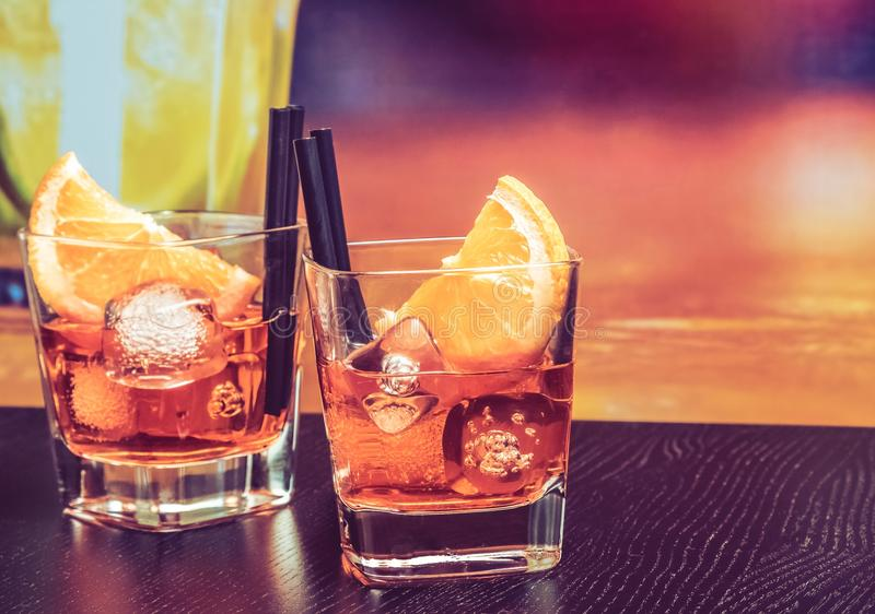 Glasses of spritz aperitif aperol cocktail with orange slices and ice cubes on bar table, vintage atmosphere background. Lounge bar concept royalty free stock images