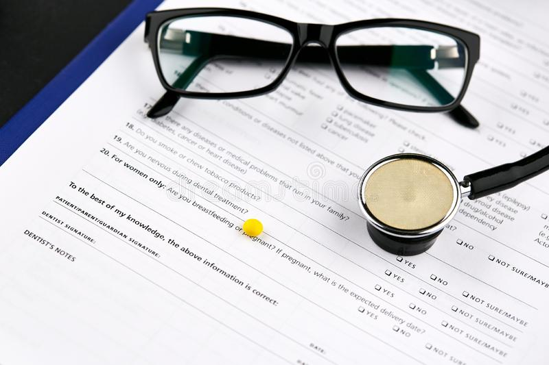 Glasses, stethoscope and yellow pill on medical questionnaire form.  royalty free stock image