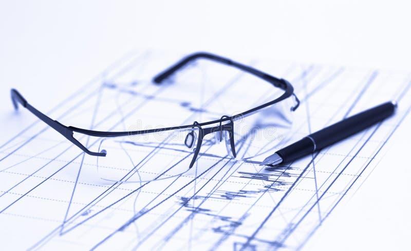 Glasses on stock chart. In blue lighting stock photo