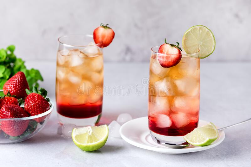 Glasses of Strawberries and Lime Ice Tea Refreshing Healthy Summer Drink Light Gray Background Horizontal.  royalty free stock photo