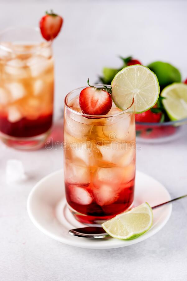 Glasses of Strawberries and Lime Ice Tea Refreshing Healthy Summer Drink Light Gray Background Vertical.  stock images