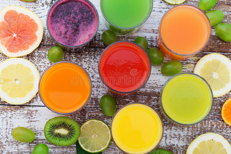 Glasses of tasty fresh juice, on wooden desk. royalty free stock images
