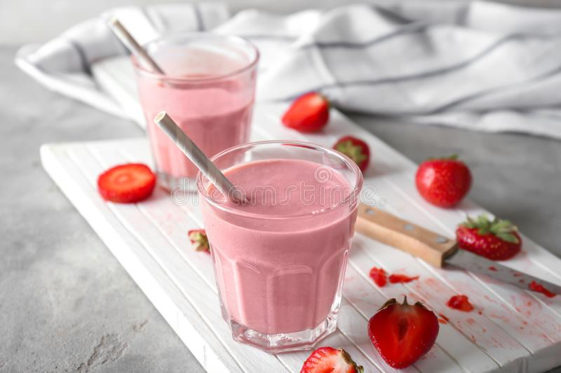 Glasses with tasty strawberry smoothie on light table stock images