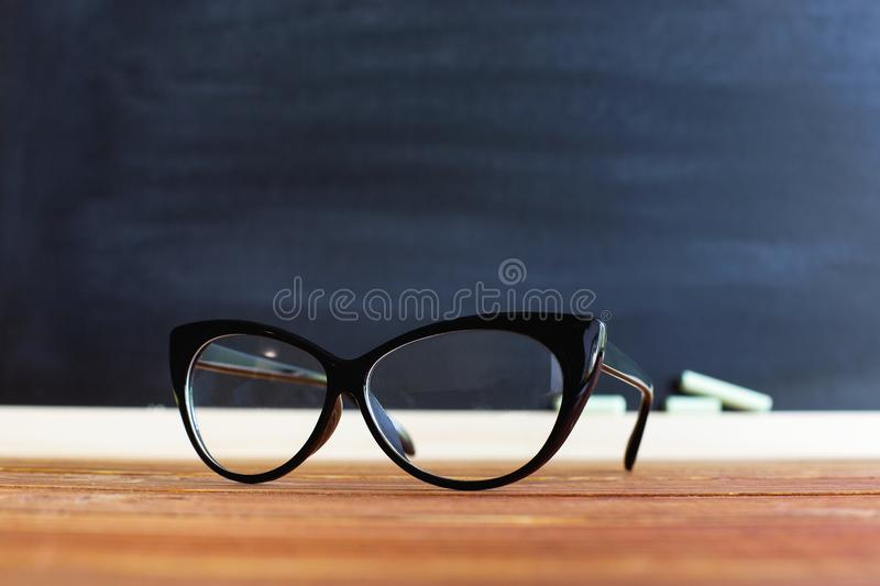 Glasses teacher on a table, against a chalkboard background with chalk. Concept for teachers day. Copy space. stock photo