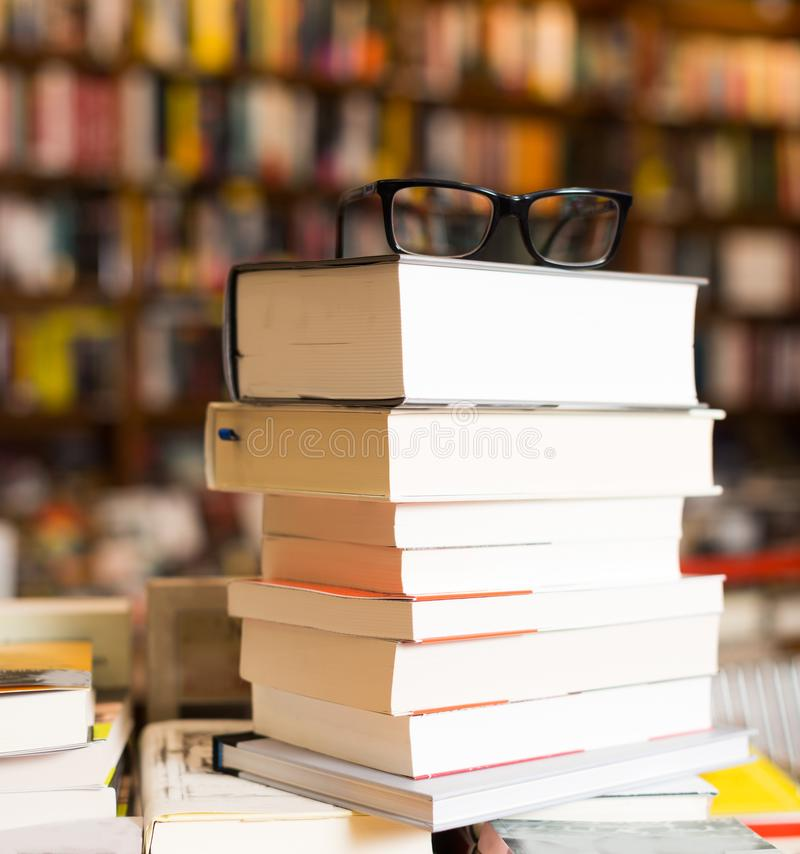 Glasses on top of stack of books lying on table in bookstore. Glasses on top of stack of art books lying on table in bookstore stock photography