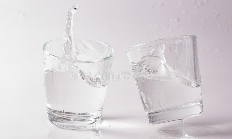 Glasses of water falling and jumping with splashes and drops.  royalty free stock photos
