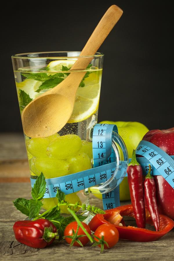 Glasses of water and a tailor`s meter. Fruits and vegetables. The concept of weight loss. Healthy diet. royalty free stock image