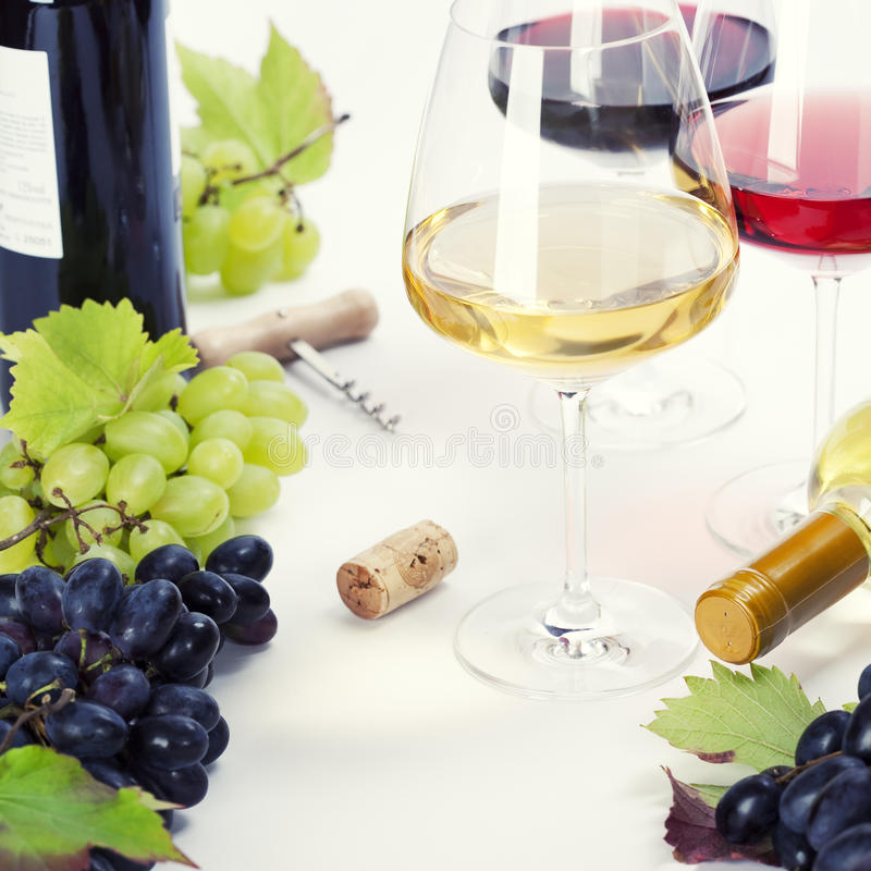 Glasses of white, red and rose wine and grapes royalty free stock image