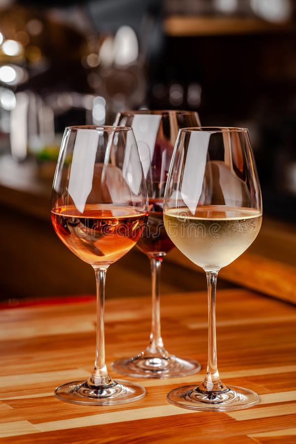 Glasses of white, rose and red wine are on the table, a bottle and corks are nearby. Glasses are on the table in the bar stock photography