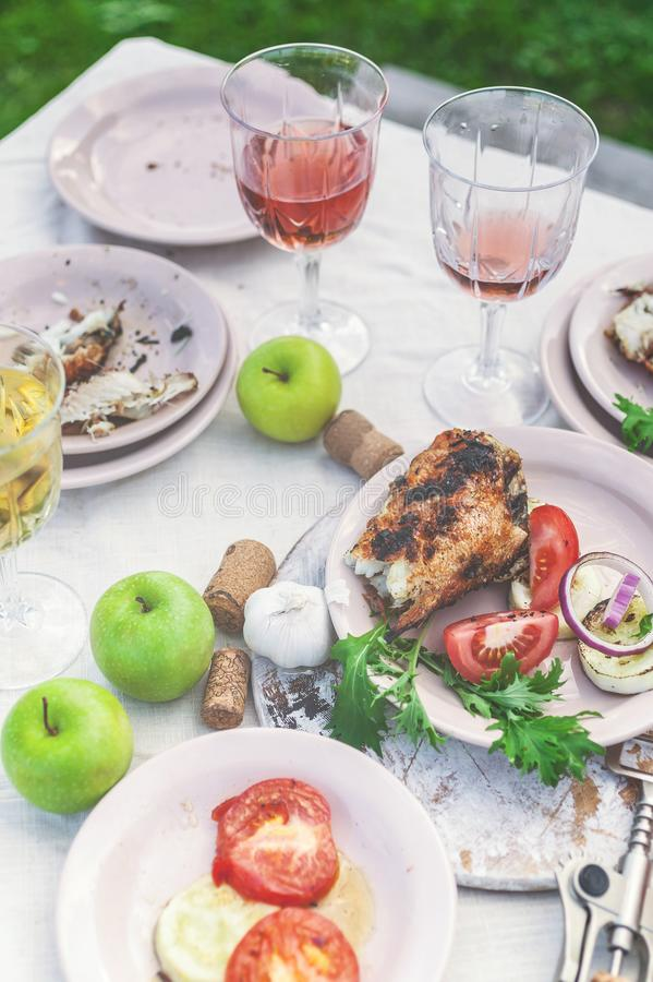 Glasses of white and rose wine, grilled fish plates, vegetables, salad and fruits on the table. Summer party in the backyard. Vertical shot royalty free stock photos