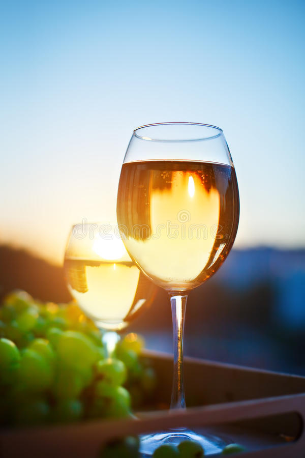 Glasses with white wine at sunset, with the reflection of the houses. stock images