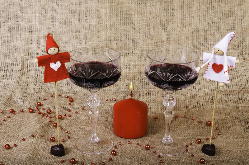 Glasses of wine, candle, chocolates and toys. royalty free stock photos