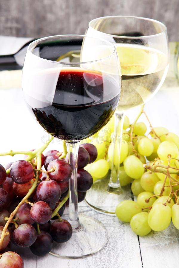 Glasses of wine and grapes on wooden background. red and white w stock photography