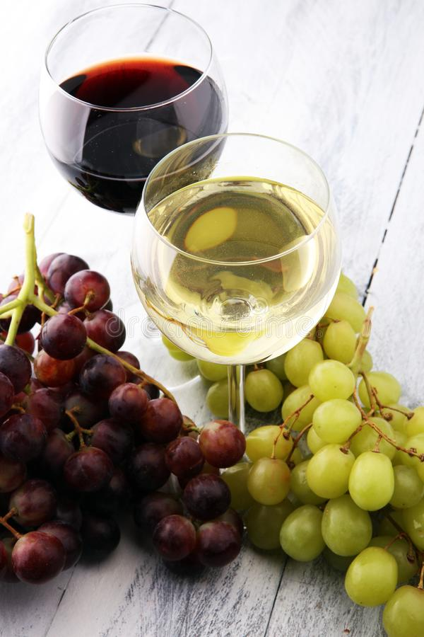 Glasses of wine and grapes on wooden background. red and white w stock image