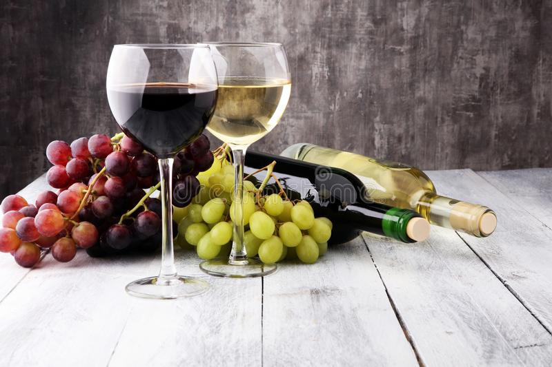 Glasses of wine and grapes on wooden background. red and white w royalty free stock images