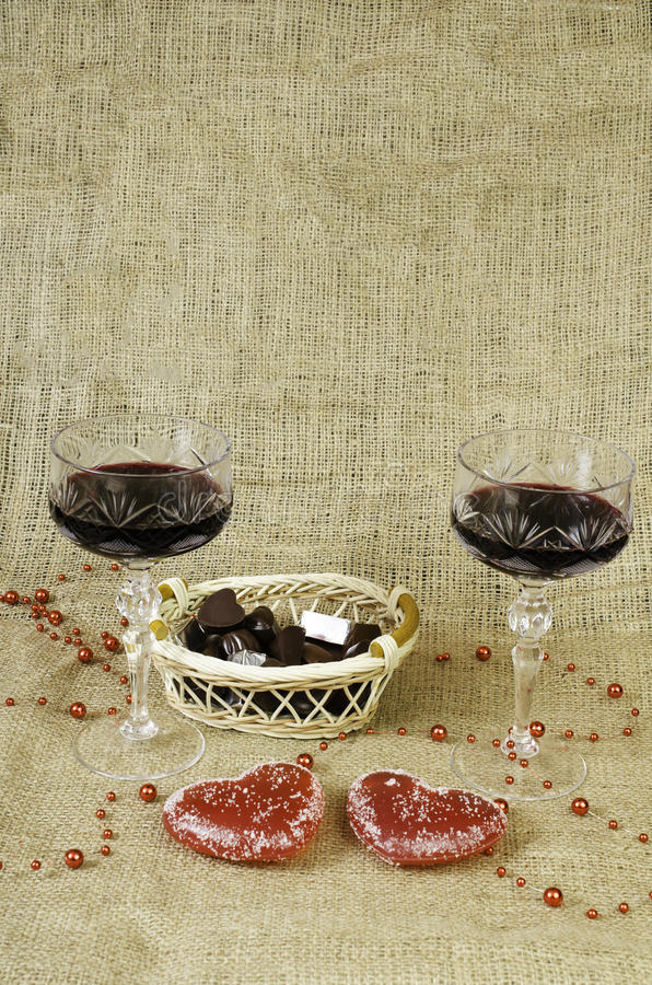 Glasses of wine, two hearts and a basket with chocolate. royalty free stock photos