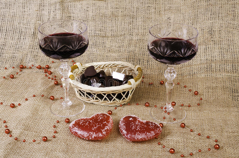 Glasses of wine, two hearts and a basket with chocolate. stock images