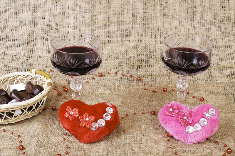Glasses of wine, two hearts and a basket with chocolate. royalty free stock photography