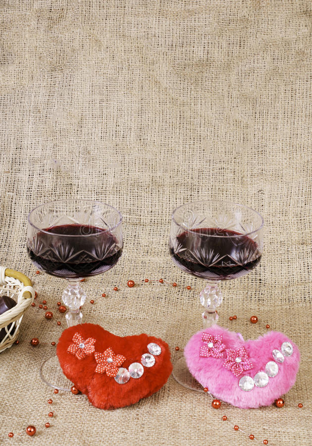 Glasses of wine, two hearts and a basket with chocolate. royalty free stock image