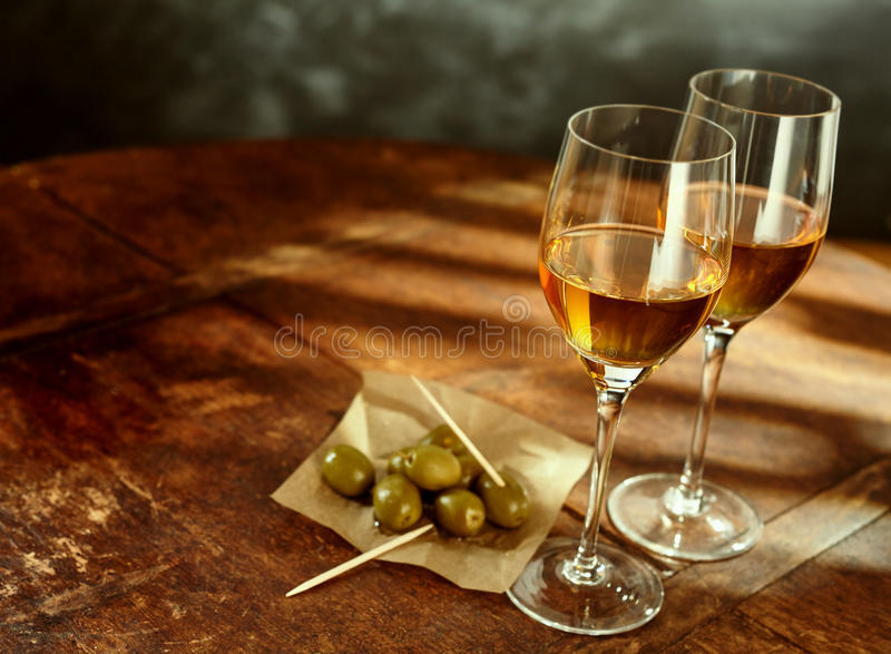 Glasses of Wine on Wood Table with Green Olives. High Angle Still Life of Two Glasses of Warm Sherry Wine on Rustic Wooden Table with Green Olives and Picks royalty free stock image