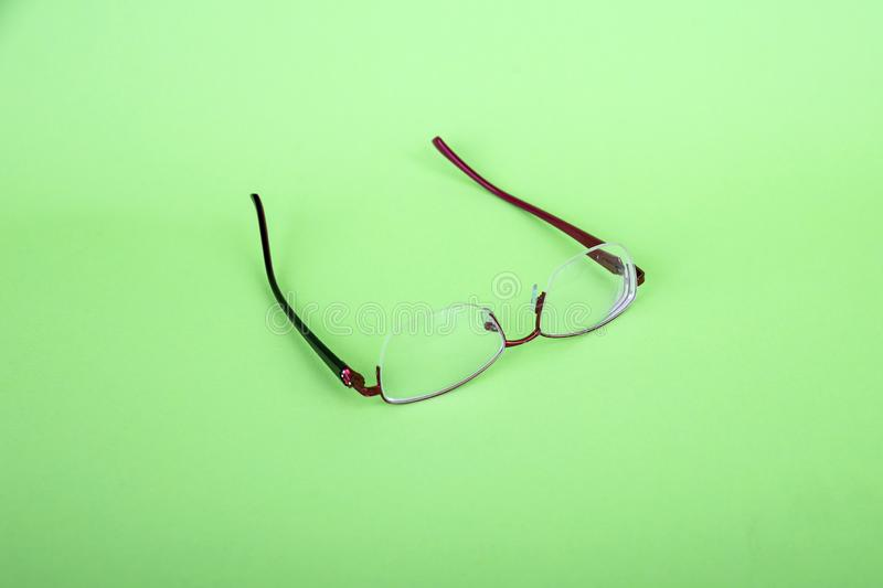 Glasses of a woman on a green background. Red frame glasses on green background. Myopia and hyperopia. Red rim glasses.  royalty free stock image