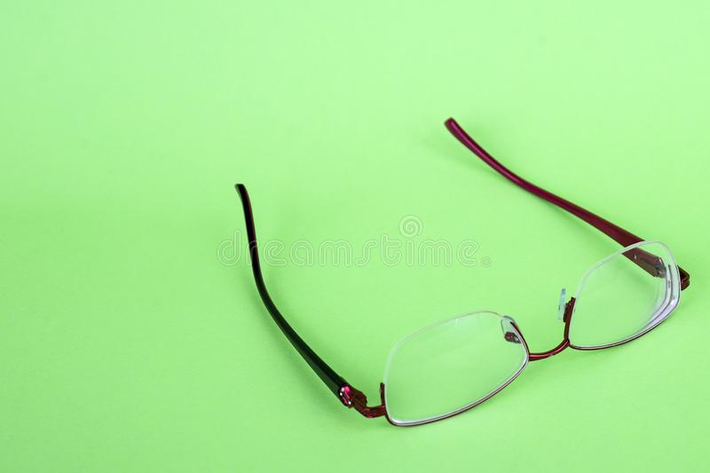 Glasses of a woman on a green background. Red frame glasses on green background. Myopia and hyperopia. Red rim glasses.  stock photo