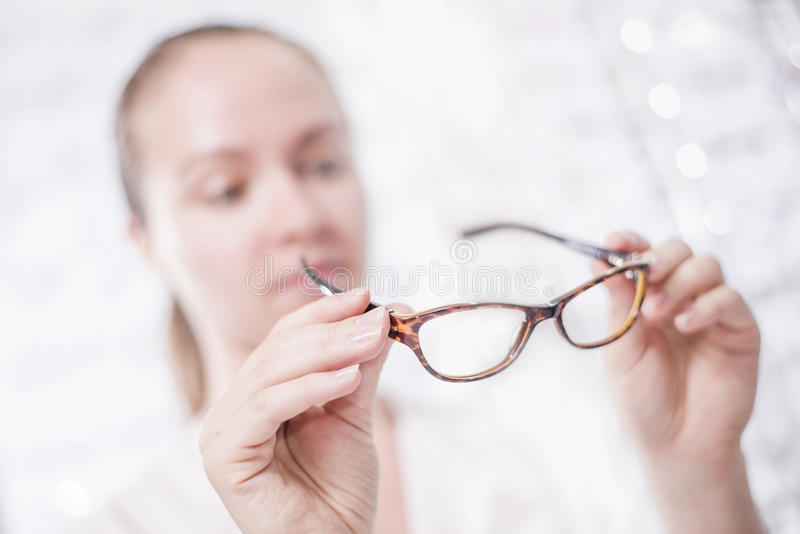 Glasses. A woman looks at her glasses stock image