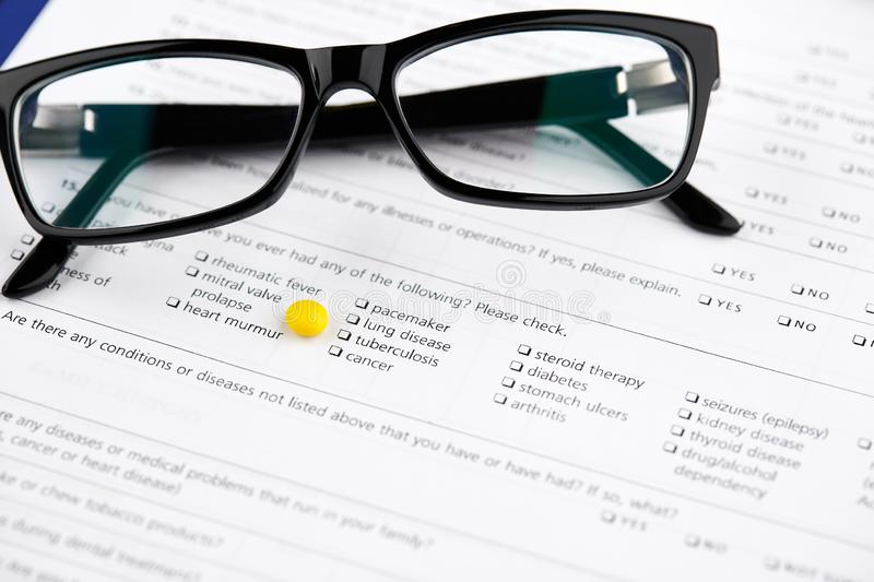 Glasses  and yellow pill on medical questionnaire form royalty free stock photo