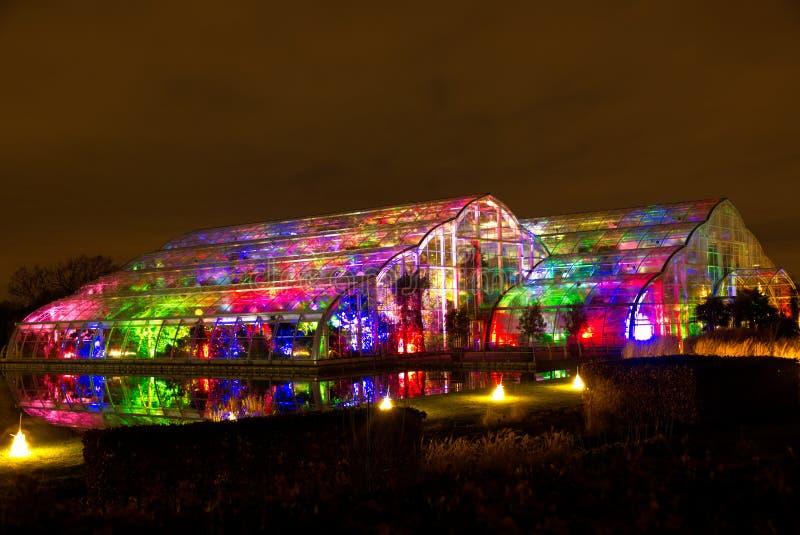 Glasshouse przy Wisley, Surrey, jarzy się z jaskrawymi coloured światłami, odbijał w wodzie obraz stock