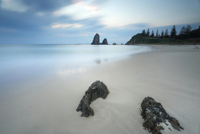 Glasshouse Rocks Australia. Long exposure taken at Glasshouse Rocks, the smooth surreal ocean and wispy clouds contrast to the sharp details of the foreground stock images